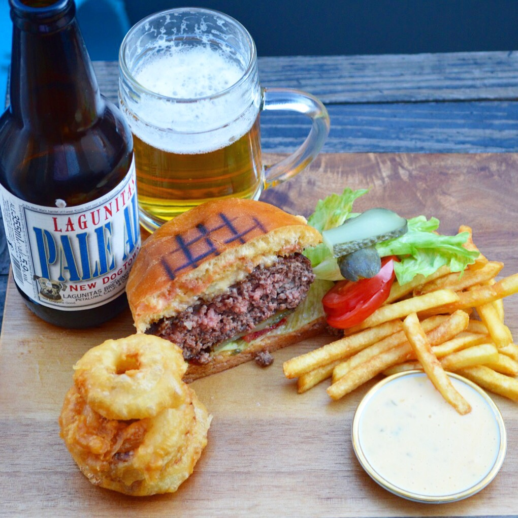 Cheeseburger with onion rings, fries, Lagunitas Pale Ale and burger sauce